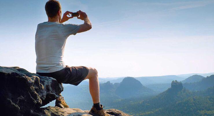 Mann auf Berg mit Kamera