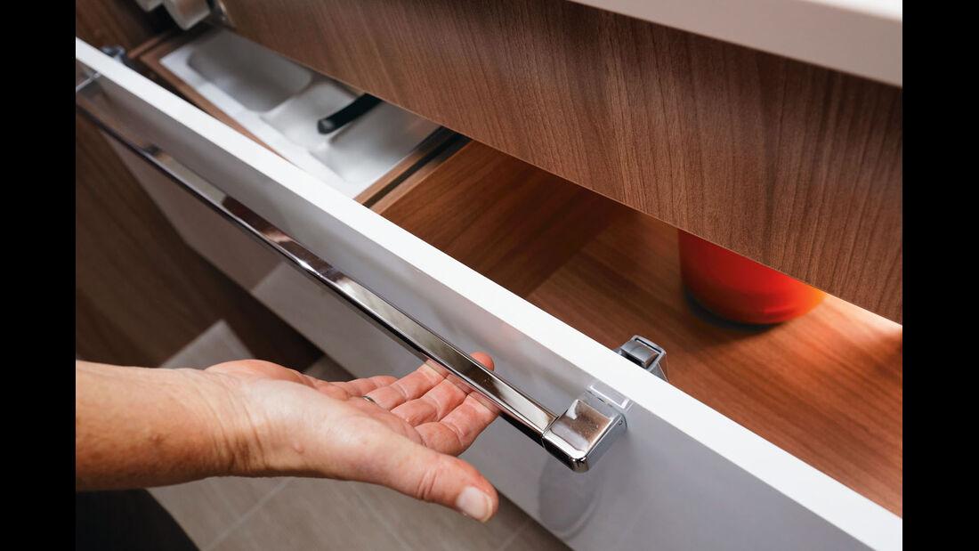 An den Küchenauszuegen fasst eine Stange zwei simple Hakenverschluesse zusammen.