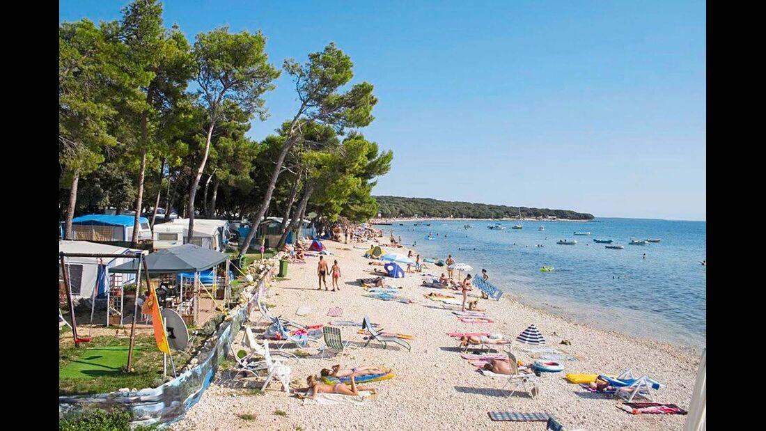An einer  schönen Bucht gelegener Platz mit kilo- meterlangem Kiesstrand, kostenfreiem  Sportzentrum und Streichelzoo für Kinder.