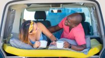 Couple young multi ethnic drinking coffee in camper van