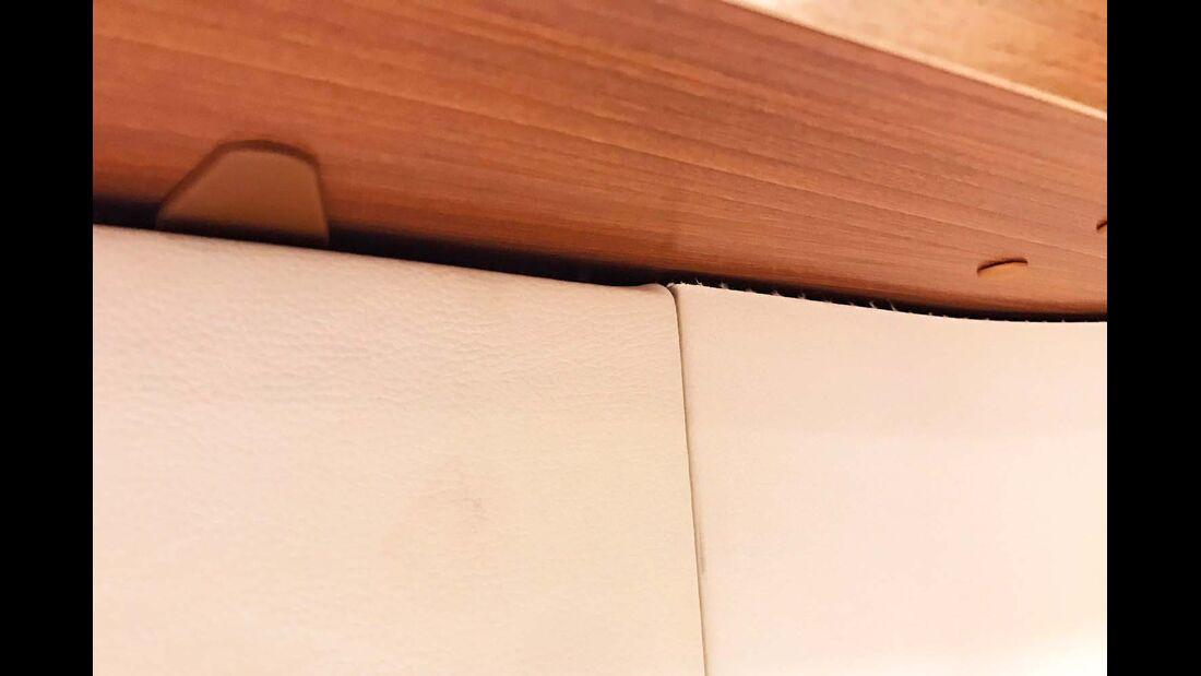 Der Kunstlederbezug am Betthaupt wirft leichte Falten und ist an den Schnittkanten fransig.