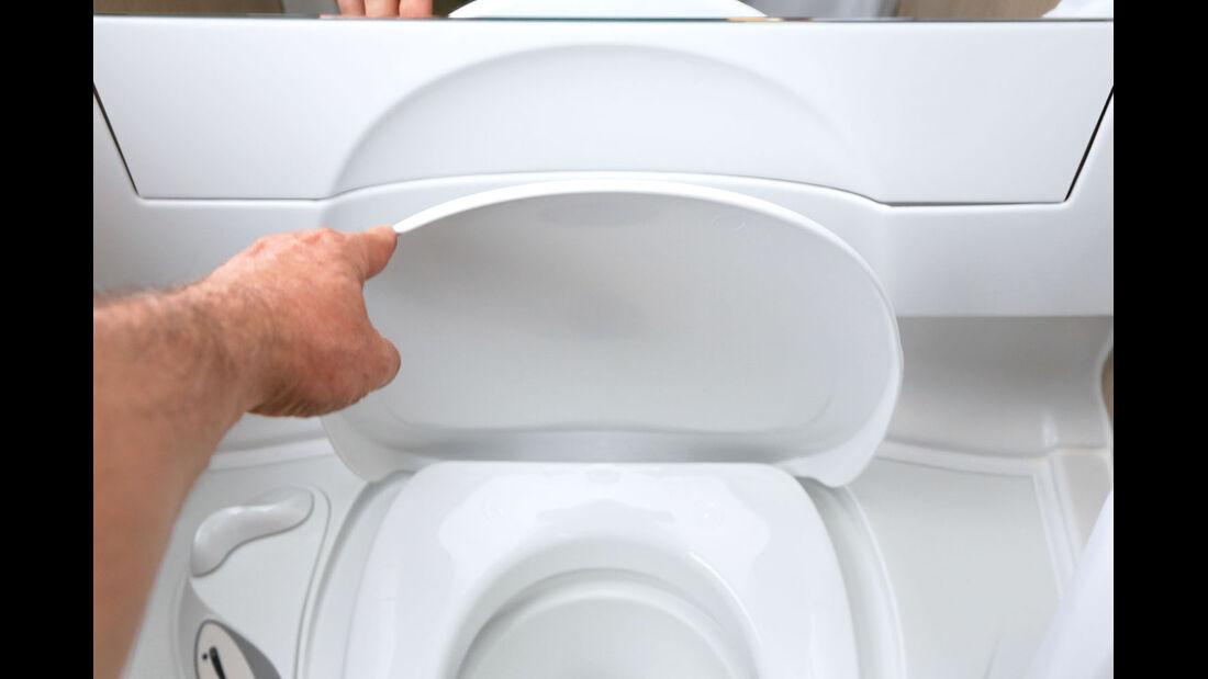 Der Toilettendeckel lehnt sich in eine Ausformung, damit er in offener Position nicht zurueckfaellt.