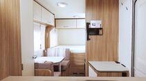 Der deckenhohe Schrank mit Staufächern und Kühlschrank schafft Platz, geht aber auf Kosten der Sitzgruppe und des Raumeindrucks.