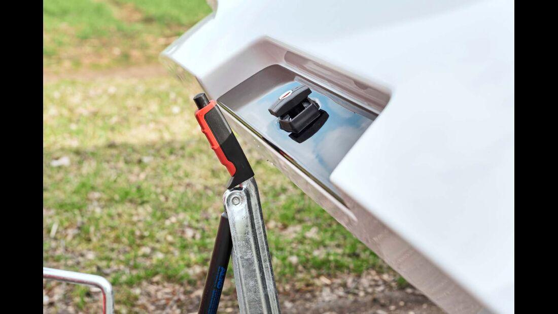 Der einfach verriegelte Gaskastendeckel bleibt beim Schließen am Handbremshebel hängen.