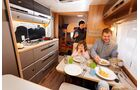 Der großen Küche mit Luxuskocher und viel Stauraum steht der schmale Tisch gegenüber.