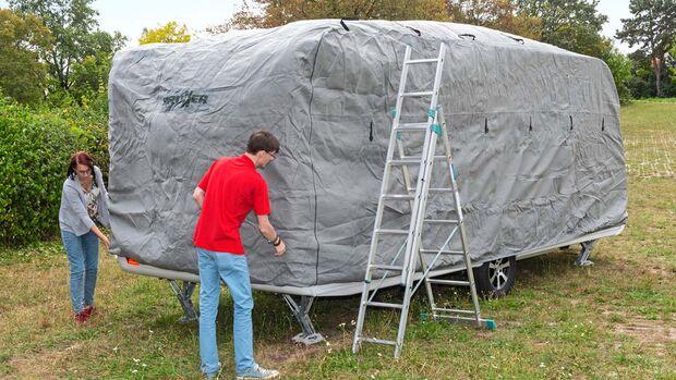 Die Schutzhülle wird von vorne nach hinten über den Caravan gezogen.