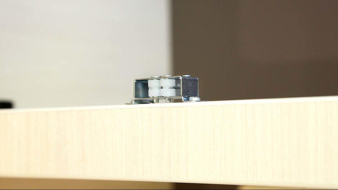 Ein einfacher Doppelrollenschnäpper hält per Kraftschluss die Klappe zu.