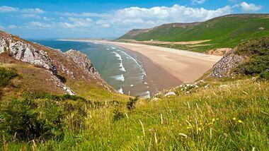 Einer der schönsten und beliebtesten Surfstrände in Wales ist der über fünf Kilometer lange Sandstrand von Rhossili Bay.