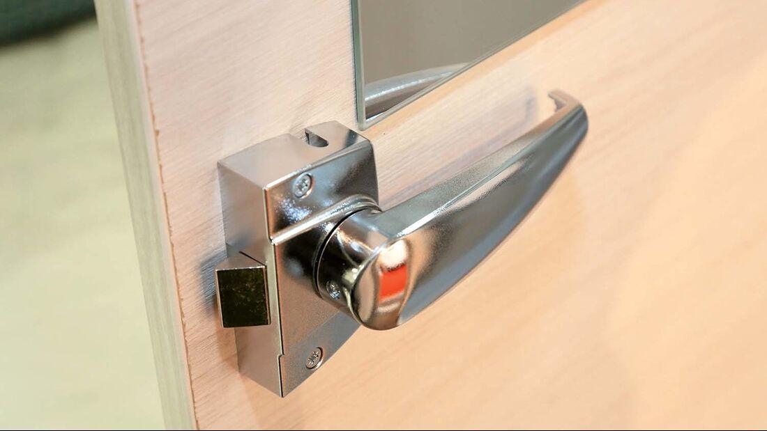 Einfaches, innen auf die Tür aufgesetztes Toilettenraumschloss, leichte Kunststoffausführung, nur zentrale Zuhaltung.