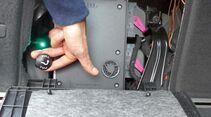 Entriegelung der Anhängekupplung im Kofferraum.