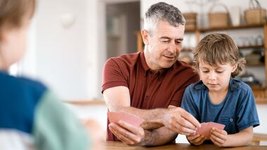 Father assisting son to play cards at home