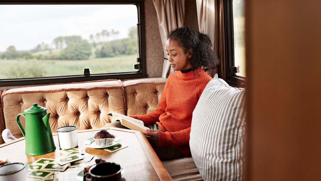 Frau lesend beim Camping