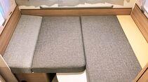 Für den Umbau der Sitzgruppe zum Bett muss ein schmales, flaches Zusatzpolster eingelegt werden.
