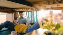 Happy young couple looking at tablet inside camper van