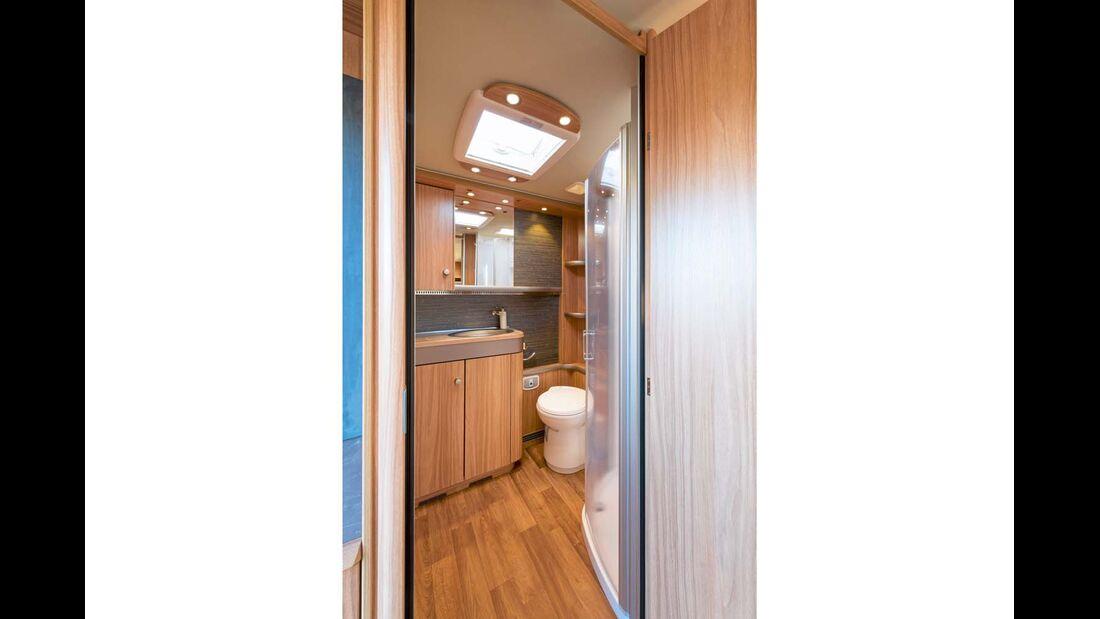 Heckbad mit separater Dusche und breiter Schrankwand gegenüber.