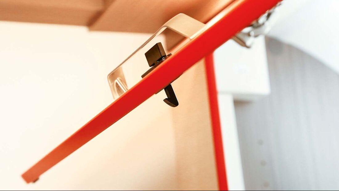 Hier ist die Drücktasten-Hakenverriegelung im Klappengriff angeordnet.