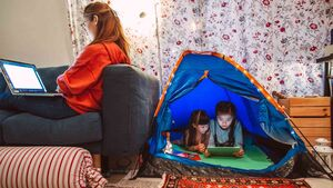 Little sisters using digital tablet in a camping tent while their mom working on laptop computer at home in the evening.