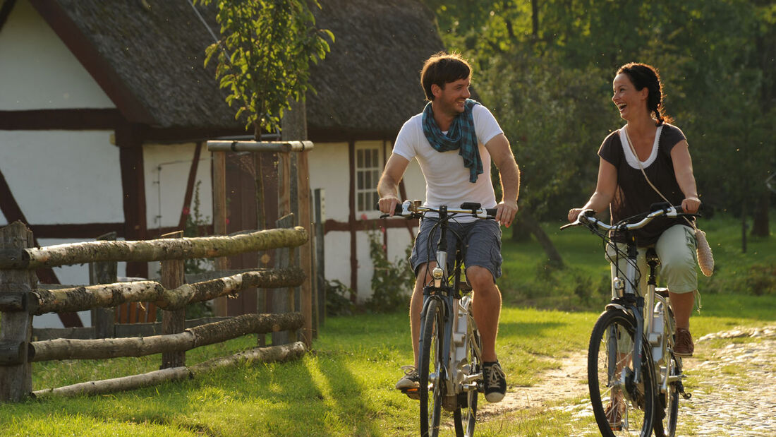 """Malerische Streuobstwiesen und reetgedeckte Fachwerkhäuser erwarten Radfahrer auf der Gartenroute """"Musische Schlossgärten"""" im Freilichtmuseum Schwerin-Mueß."""