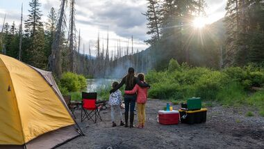Mother and daughters bonding while camping in nature
