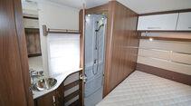 Parallel zum Bett erstreckt sich der Sanitärbereich mit Dusch- und Toilettenraum.