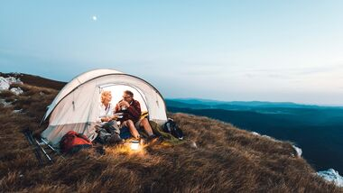 Senior couple camping in the mountains and eating a snack