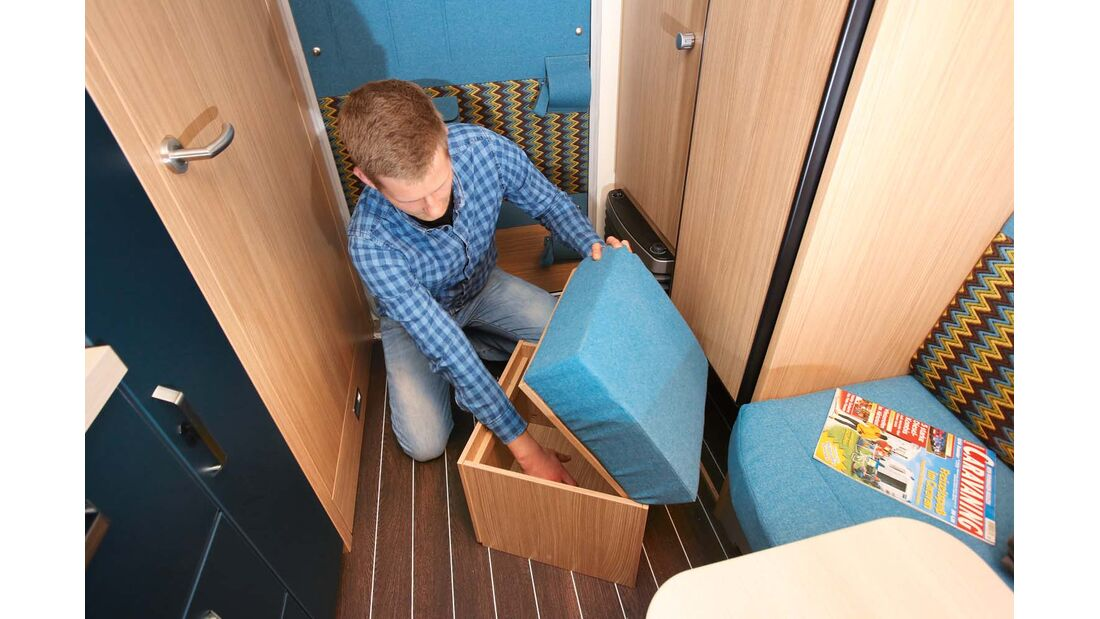 Sitzwürfel dient als zusätzlicher Staukasten und rastet während der Fahrt mit abgenommenem Polster sicher unterm Kühlschrank ein im Knaus Sport & Fun