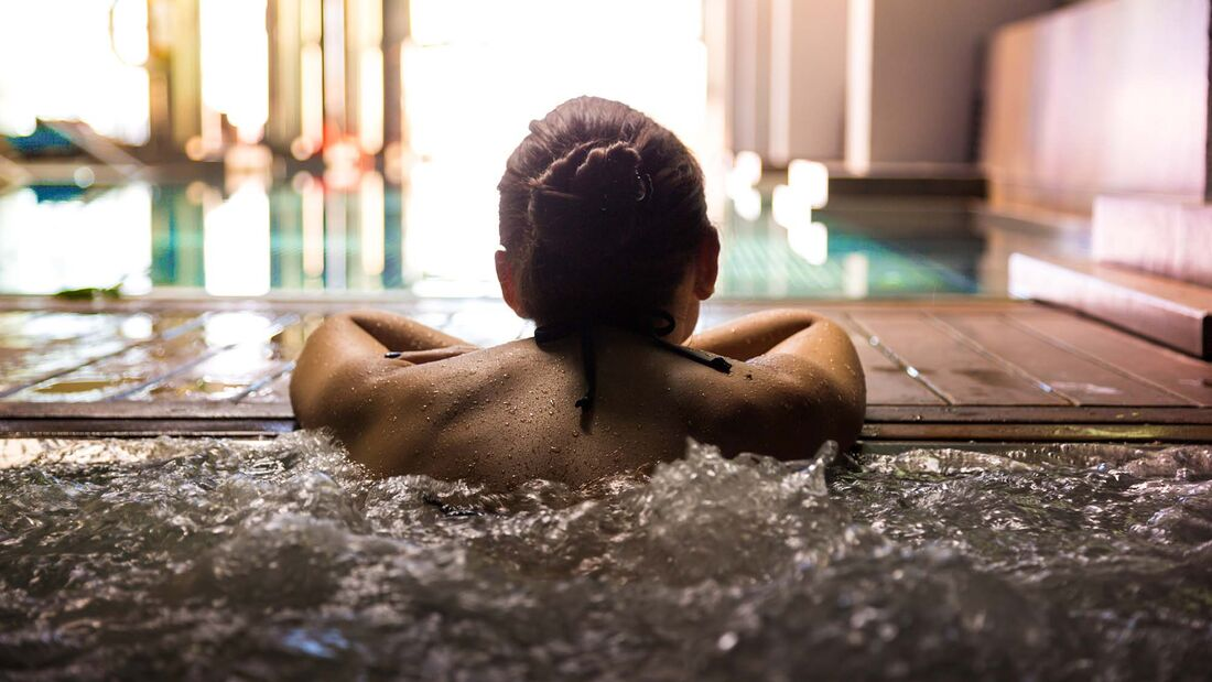 Woman relaxing in a hot tub pool during weekend days of relax and spa in a luxury place during travel vacations.