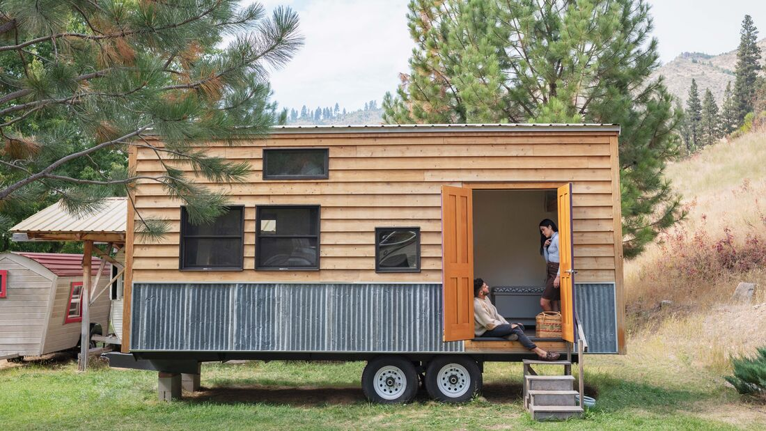 Young couple talking in doorway of their tiny house